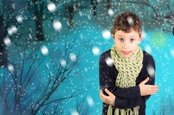 Little boy feeling cold in a winter park while snow falling