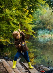 Little boy fisherman fishing in a lake with a fishing rod. Excited kid fishing on weekend