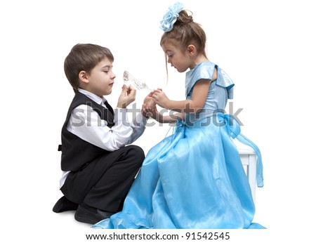Little boy fitting a glass slipper onto a beautiful little girl
