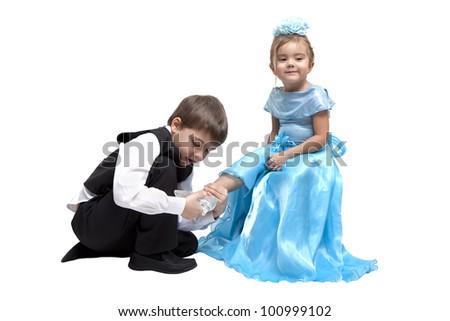 Little boy fitting a glass slipper onto a little girl
