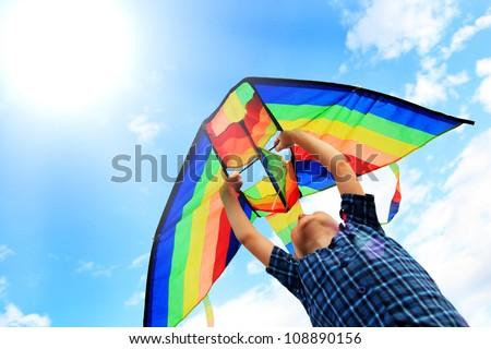 Little boy flies a kite into the blue sky