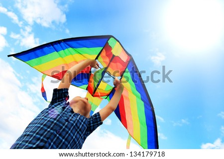 Little boy flies a kite into the blue sky