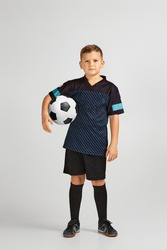 little boy football player in uniform holding ball over studio background. child dreams of becoming a soccer player.