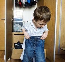 Little boy getting dressed by himself