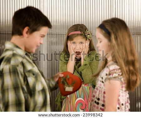 Little boy giving a candy heart to girl causes anger - stock photo