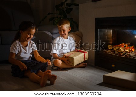 Little boy giving a giftbox with red ribbon to girl, siblings sitting near a fireplace