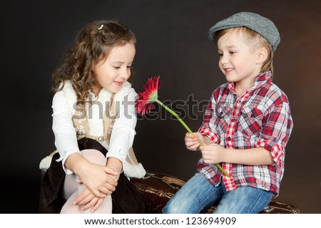Little boy giving a red flower to a beautiful smiling little girl. Valentine day