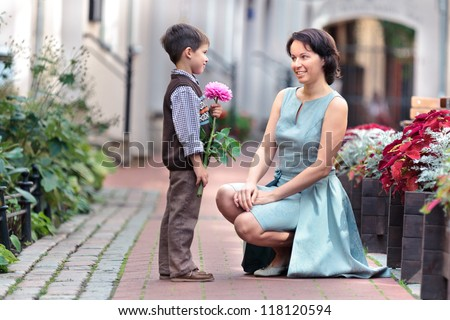 Little boy giving flower to his mom on mother\'s day