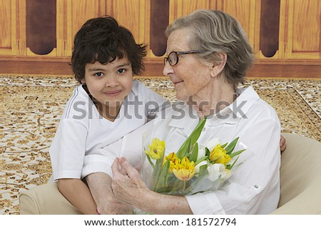 Little boy giving flowers to his grand mother