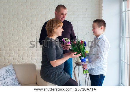 Little boy giving flowers to his mom on mother\'s day