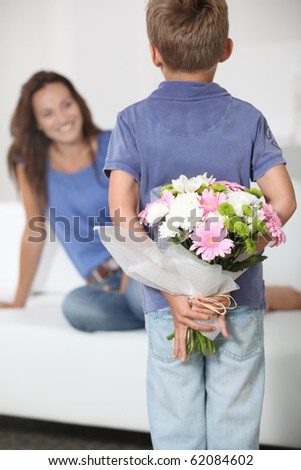 Little boy giving flowers to his mom on mother's day