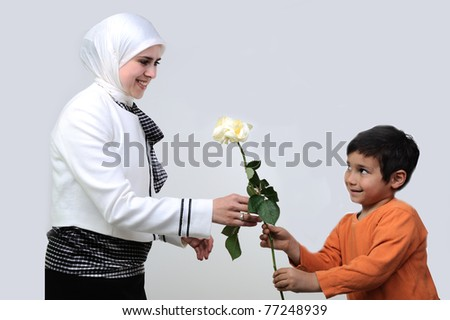 Little boy giving flowers to mom on mother's day, islamic clothes