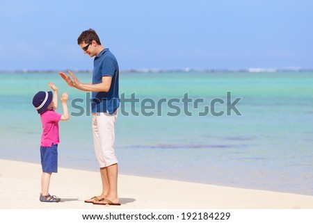 little boy giving his father high five at the beach, spending fun day together during summer vacation