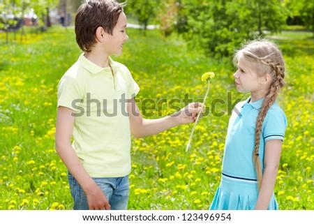 Little boy giving yellow dandelion to cute girl outdoor