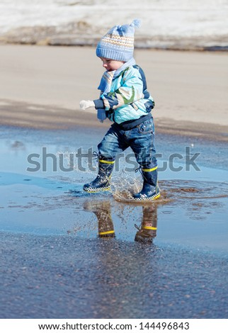 little boy goes on a pool in rubber boots