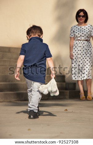 Little boy going with bowed head to Mom