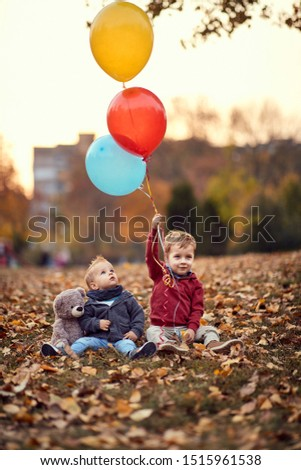 Little boy. Golden autumn. Sunny day. boys smiling boys playing with balloons in the autumn park. #1515961538