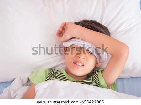 Little boy had high fever with towel over his head laying in the bed