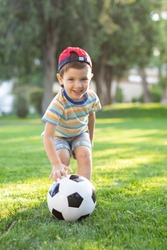 Little boy happy kid playing football and ready to kick the ball on green grass with copyspace