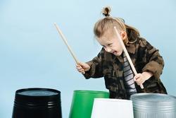 Little boy having fun, he using drumsticks on iron and plastic buckets. Playing rhythm.