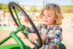 Little Boy Having Fun In A Tractor in a Rustic Ranch Setting at the Pumpkin Patch.