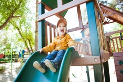 Little boy having fun on a playground outdoors in summer. Toddler on a slide.