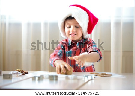 Little boy helping at kitchen with baking cookies