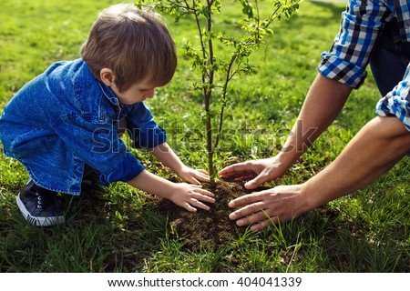 little boy helping his father to plant the tree while working together in the garden. sunday. smiling face.  spring time