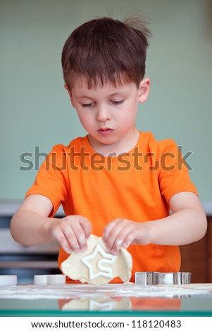 Little boy helping with baking cookies in the kitchen - stock photo