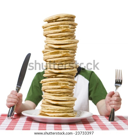 Little boy hidden behind  a giant plate of pancakes, with a knife and fork visible on a table cloth.