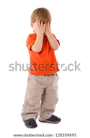 Little boy hide face under hands, playing hide-and-seek, isolated on white