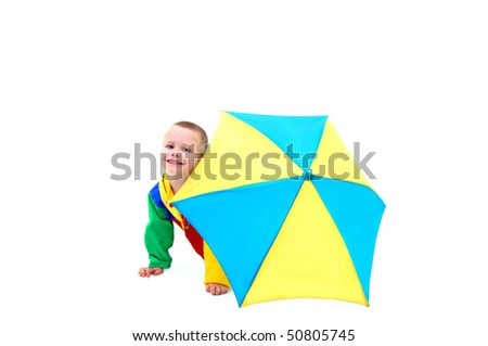 Little boy hides behind a colorful umbrella waiting for April showers to be over.  He is wearing a colorful raincoat and behind a yellow and blue umbrella.