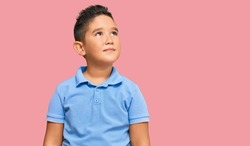 Little boy hispanic kid wearing casual clothes smiling looking to the side and staring away thinking.
