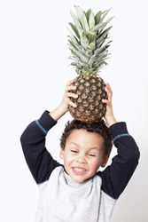 little boy holding a pineapple on his head and smiling white background  stock photo