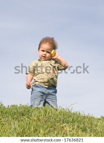 Little boy holding a toy cellphone near his ear