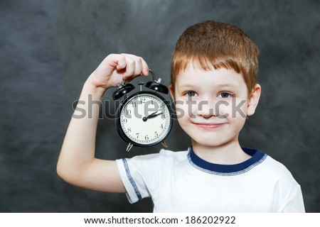 Little boy holding alarm clock.