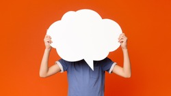 Little boy holding an empty speech bubble in front of his head, orange studio background, free space