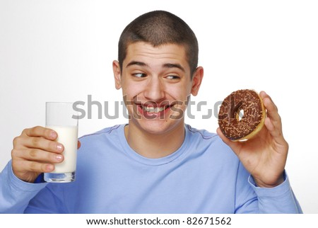 Little boy holding and eating a chocolate donuts and drinking milk on white background.