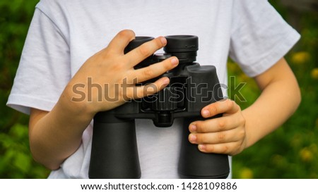little boy holding binoculars in hands for exploring for Knowledge #1428109886