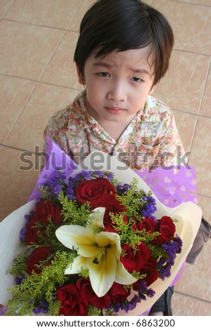 Little boy holding bouquet of red roses and lily