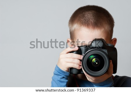 Little Boy holding camera and taking photo. White Background.