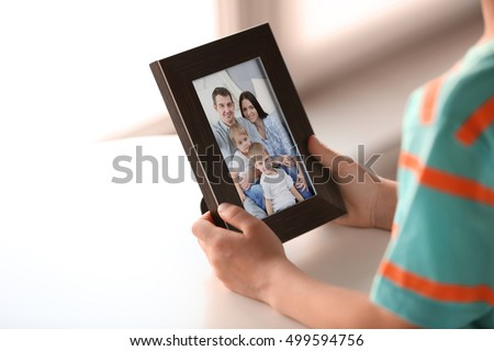 Little boy holding photo frame with picture of family. Happy memories concept.