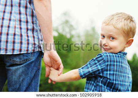Little boy holding the hand of his father