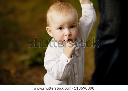 little boy holds parent by hand