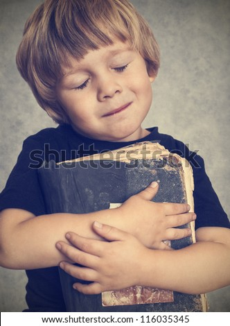 Little boy hugging an old book, he is happy - stock photo