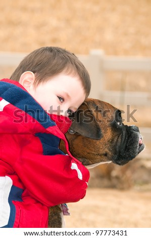 Little boy hugging his best friend, the family pet Boxer. After playing hard in the back yard two pals stop to rest.