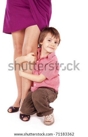 Little boy hugging the leg of his young mum