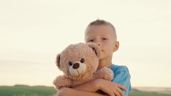 Little boy hugs his favorite soft bear toy on the playground. The child plays with the Teddy bear. Plush toy in the hands of kid in summer park. Kid plays with a toy and dreams outdoors. Best friends