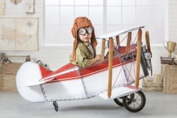 Little boy imagines himself as an airplane pilot in the children's room.