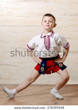 Little boy in a colorful costume practicing a dance or ballet pose with his leg outstretched and a pleased expression